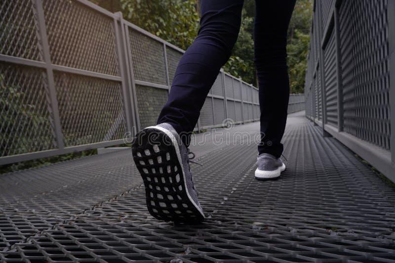 Nikła kobieta chodzi wzdłuż lasowego śladu iść na piechotę w niebieskich dżinsach i popielatych sneakers obrazy royalty free