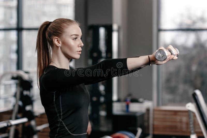 Nikła młoda dziewczyna ubierająca w czarnym sportswear robi ćwiczeniom z dumbbells w nowożytnym gym z udziałami sport zdjęcia stock