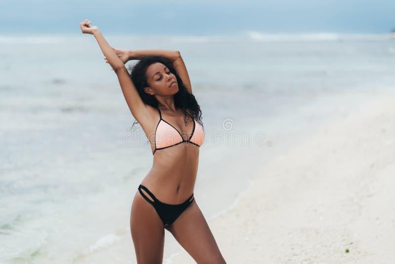 Nikły seksowny zmrok skinned dziewczyny w swimwear pozuje na plaży z piaskiem obrazy royalty free