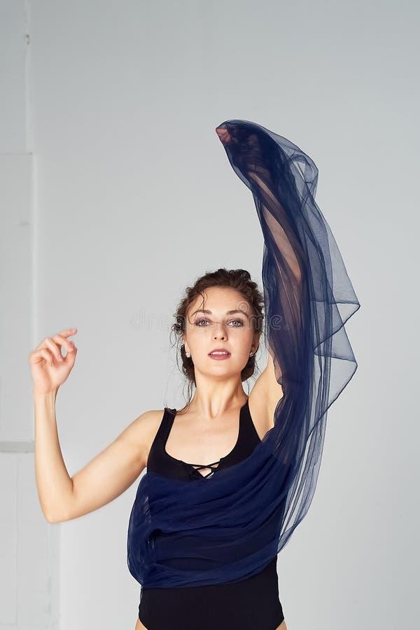 Nikła gimnastyczka w czarnych rajstopy tanczy z błękitnym szyfonem który rozwija Estetyka taniec obraz royalty free