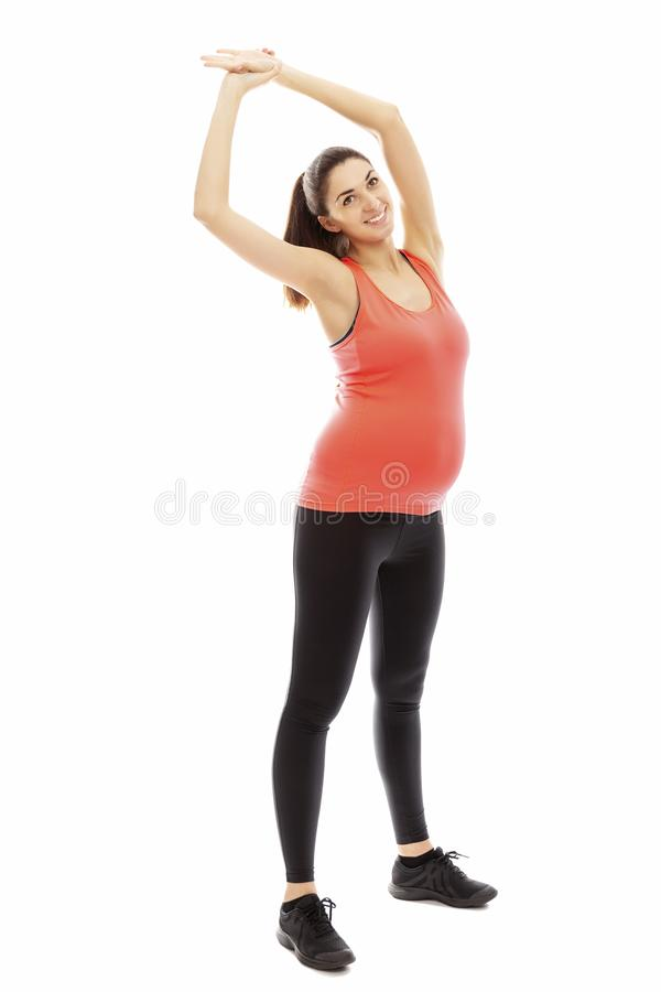 Nikła kobieta w ciąży angażował w fizycznej edukacji, pełny przyrost pojedynczy bia?e t?o zdjęcia royalty free