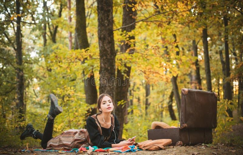 Nikła piękna młoda kobieta odpoczywa w jesieni w parku Cieszyć się muzykę i picnicking Rocznika pinkinu akcesoria zdjęcia royalty free