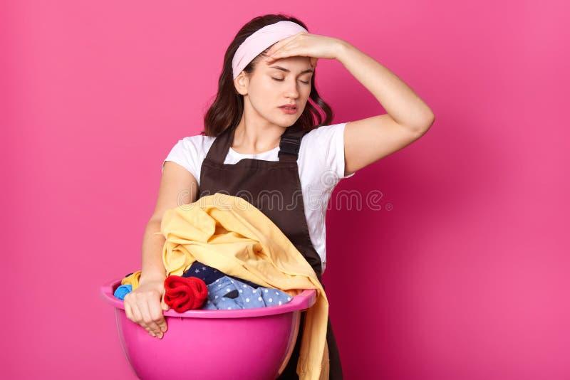Nikła stresująca młoda kobieta stawia jej rękę na głowie, trzymający basenowy z brudnym odziewa, zamykający ona oczy, wyc zdjęcie stock
