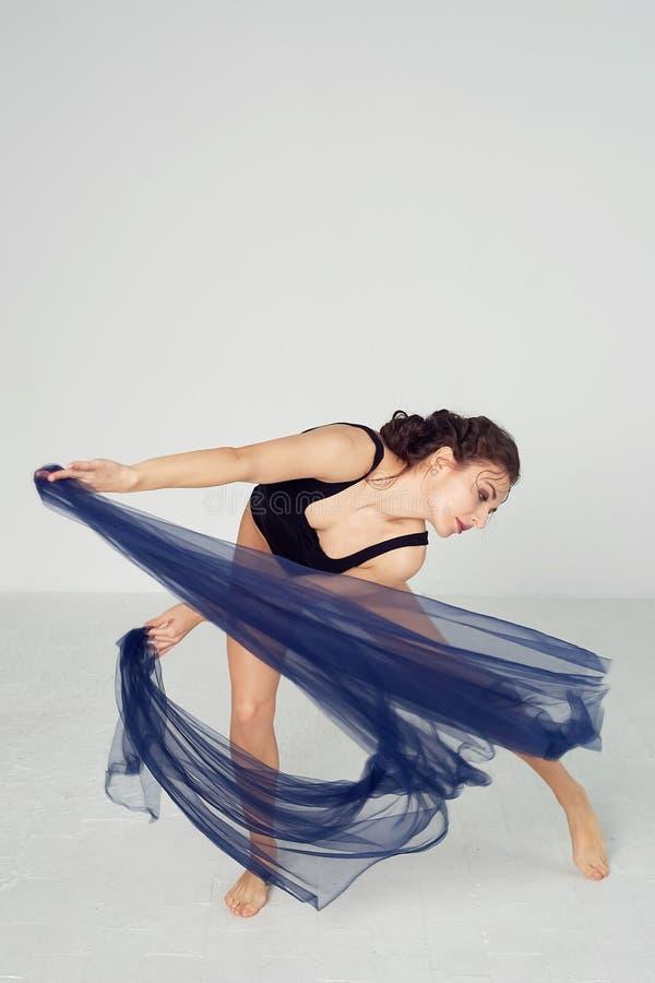 Nik?a gimnastyczka w czarnych rajstopy tanczy z b??kitnym szyfonem kt?ry rozwija Estetyka taniec zdjęcia royalty free