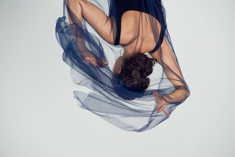 Nik?a gimnastyczka w czarnych rajstopy tanczy z b??kitnym szyfonem kt?ry rozwija Estetyka taniec zdjęcie stock