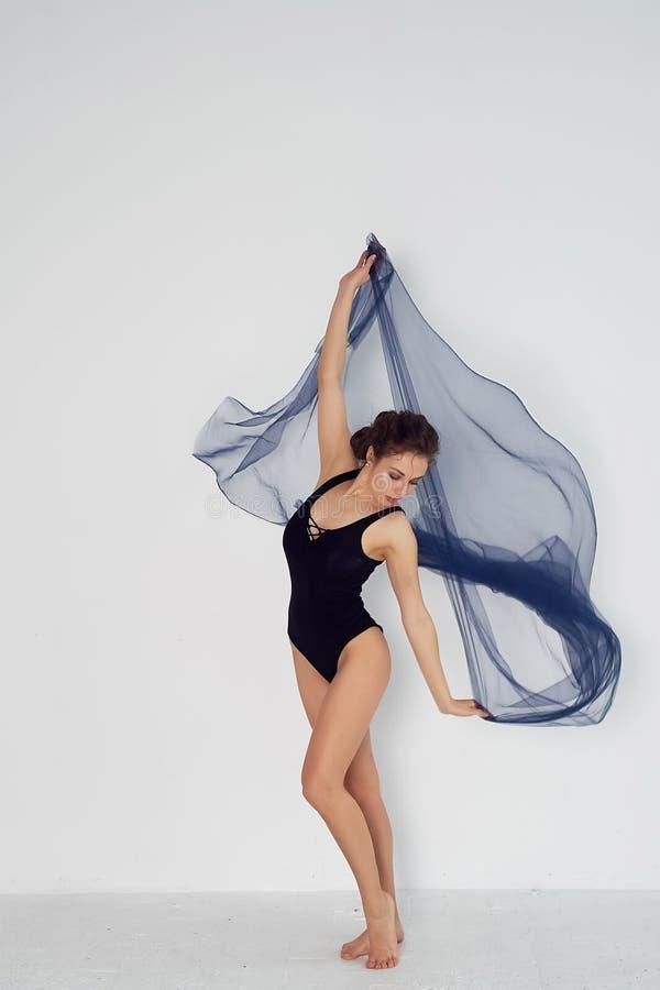 Nik?a gimnastyczka w czarnych rajstopy tanczy z b??kitnym szyfonem kt?ry rozwija Estetyka taniec fotografia stock