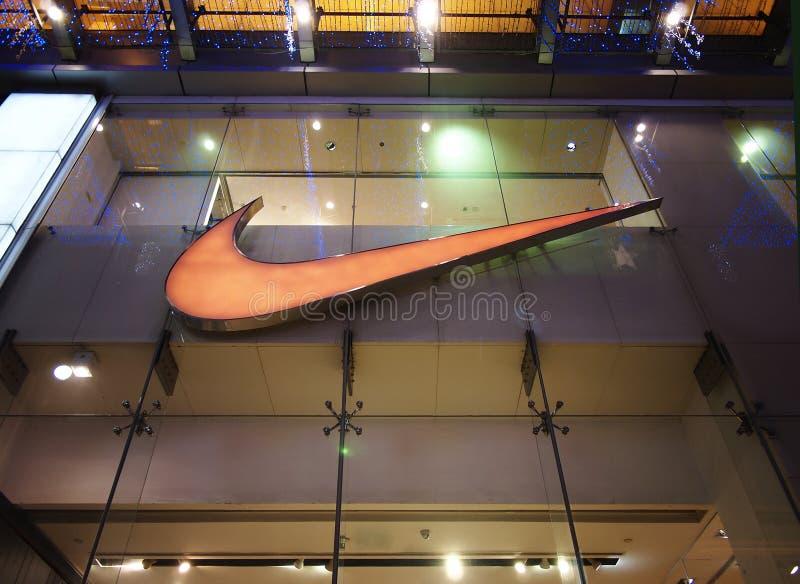 Nike lagerlogo på väggen arkivbilder