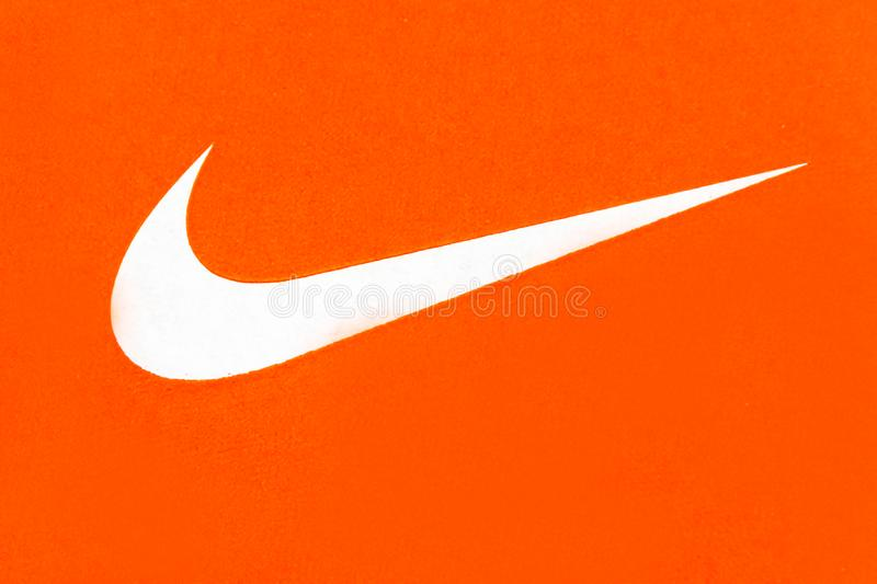 Nike Swoosh, business symbol or sign. White Nike Logo on Orange Background;Nike, Inc. is an American multinational corporation that is engaged in the design stock photography