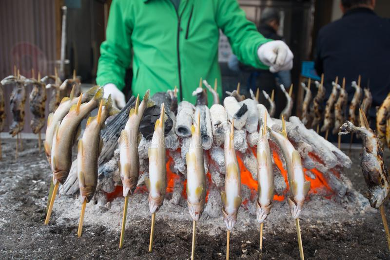 Charcoal grilled Ayu fish with salt. Traditional Japanese street food at Kegon waterfall in Nikko, Japan stock photos
