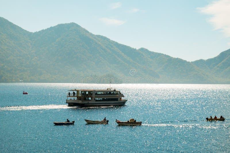 Nikko Japan - Oktober 2015: Abschluss oben von touristischen Schiffs- und Fischenmannbooten sind im See ChuzenjiChuzenjiko in Nik stockbild