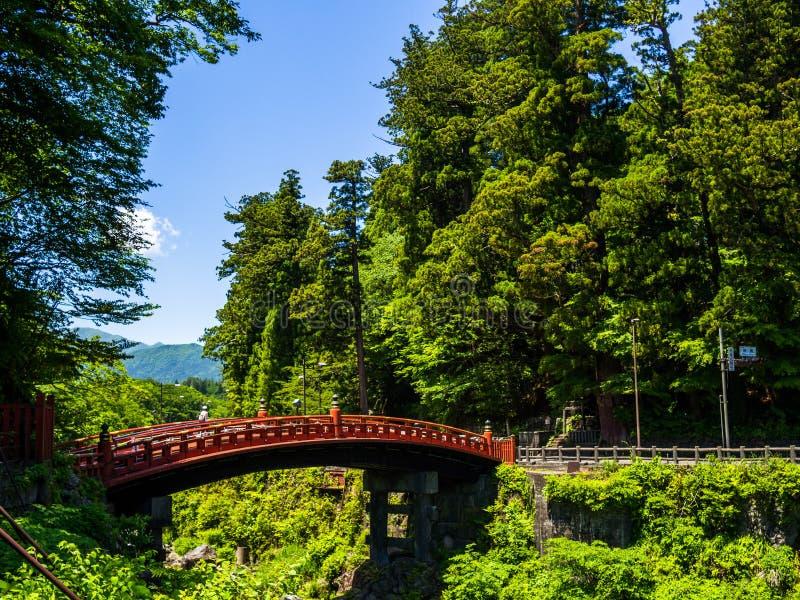 NIKKO JAPONIA, SIERPIEŃ, - 14, 2017: Czerwony Antyczny most Shinkyo most nad Daiwa rzeką na pięknym słonecznym dniu zdjęcie stock