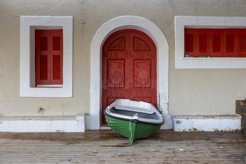 Green fishing boat in front of a red door in Agios Nikolaos in Crete Greece. Nikolaos Crete, 18-12-2018. Green fishing boat in front of a red door in Agios stock image