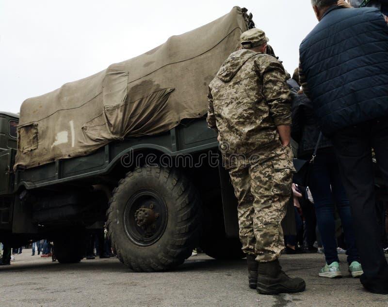NIKOPOL, DE OEKRA?NE - MAG, 2019: Oekra?ense militair is over een legervrachtwagen stock afbeeldingen
