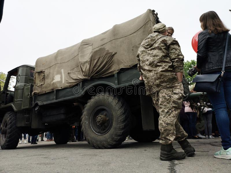 NIKOPOL, DE OEKRA?NE - MAG, 2019: Oekra?ense militair is over een legervrachtwagen royalty-vrije stock foto's