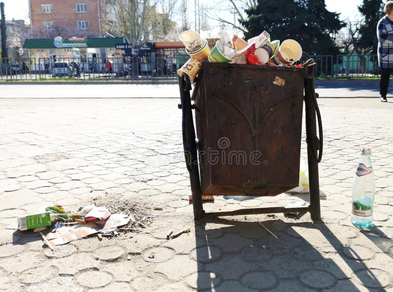 Nikopol, Ucrania, el 20 de mayo de 2019: un bote de basura apretado en la calle ucraniana, con basura en las losas foto de archivo