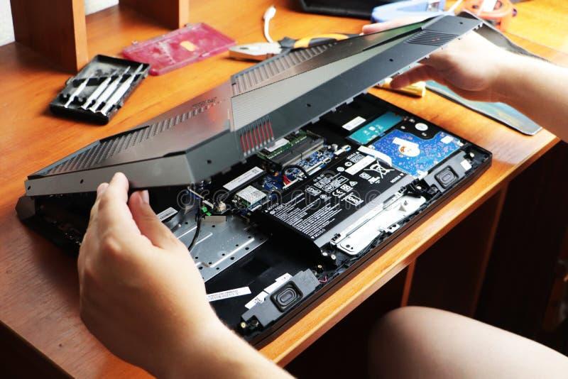 NIKOPOL, UCRANIA - JUNIO DE 2018: El control del técnico el destornillador para reparar el ordenador, el concepto de hardware, imagen de archivo libre de regalías