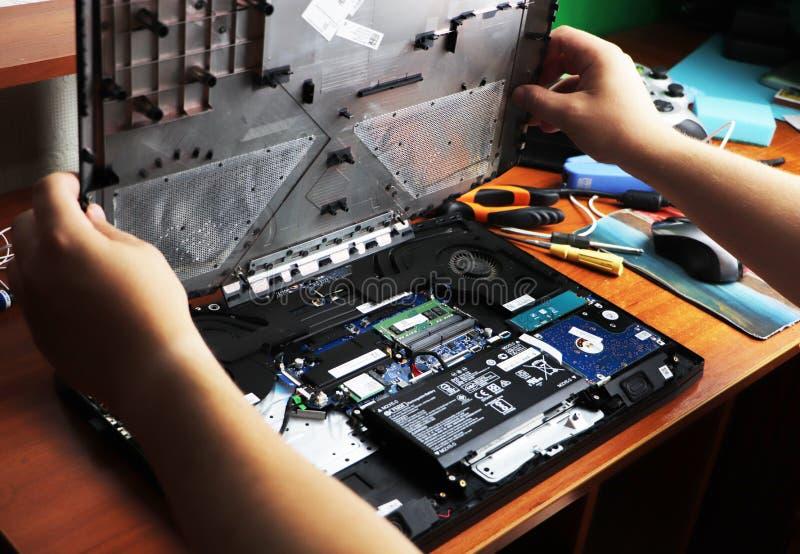 NIKOPOL, UCRANIA - JUNIO DE 2018: El control del técnico el destornillador para reparar el ordenador, el concepto de hardware, fotografía de archivo