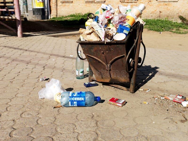 Nikopol, Ukraina, Maj 20, 2019: zat?oczony kube? na ?mieci na Ukrai?skiej ulicie z ?mieci na brukowych cegie?kach, obraz stock