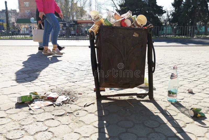 Nikopol, Ukraina, Maj 20, 2019: zat?oczony kube? na ?mieci na Ukrai?skiej ulicie z ?mieci na brukowych cegie?kach, fotografia royalty free
