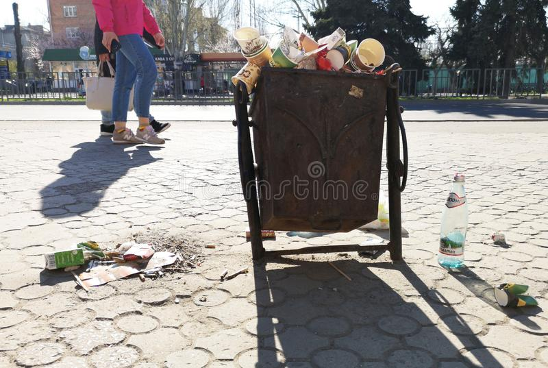 Nikopol, Ukraine, am 20. Mai 2019: ein gedr?ngter Abfalleimer auf der ukrainischen Stra?e, mit Abfall auf Pflastersteinen lizenzfreie stockfotografie