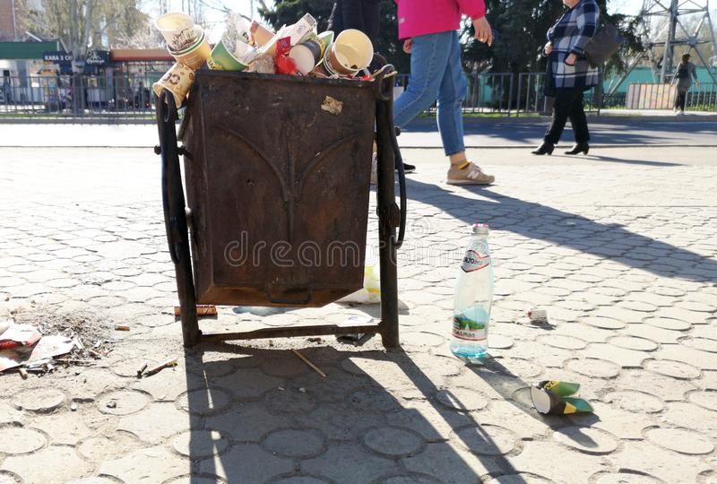 Nikopol, Ukraine, am 20. Mai 2019: ein gedr?ngter Abfalleimer auf der ukrainischen Stra?e, mit Abfall auf Pflastersteinen lizenzfreies stockbild