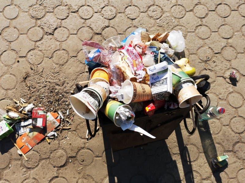 Nikopol, Ukraine, am 20. Mai 2019: ein gedr?ngter Abfalleimer auf der ukrainischen Stra?e, mit Abfall auf Pflastersteinen lizenzfreies stockfoto