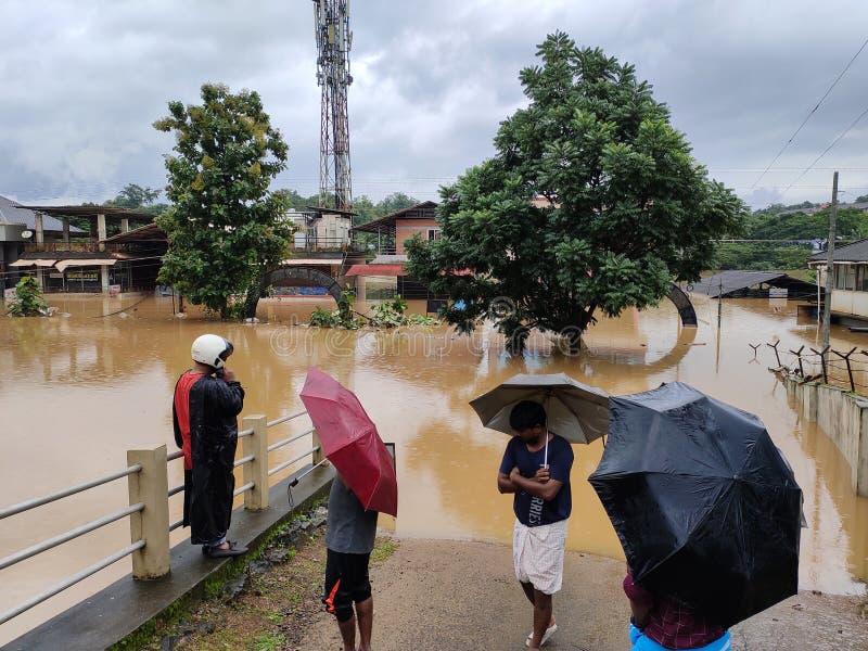 2019 flood in Nilambur, Kerala. NILAMBUR, KERALA, INDIA - AUGUST 09, 2019: People gathered near the flood affected street in Janathapadi, Nilambur. Shops and royalty free stock photo