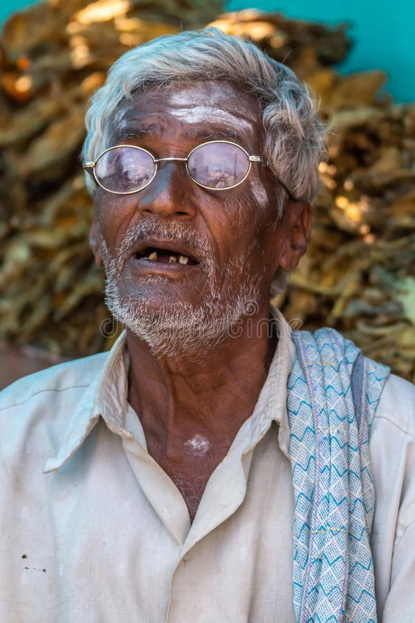Old man with bad teeth, Nilavagilukaval Karnataka India. Nilavagilukaval, Karnataka, India - November 1, 2013: Closeup of old graying man with open mouth stock image