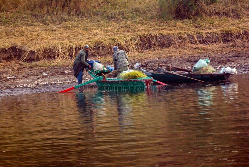 Nile River, cerca de Aswnm, Egipto, el 21 de febrero de 2017: Dos pescadores egipcios turbaned que agitan su bote pequeño en el b fotografía de archivo libre de regalías