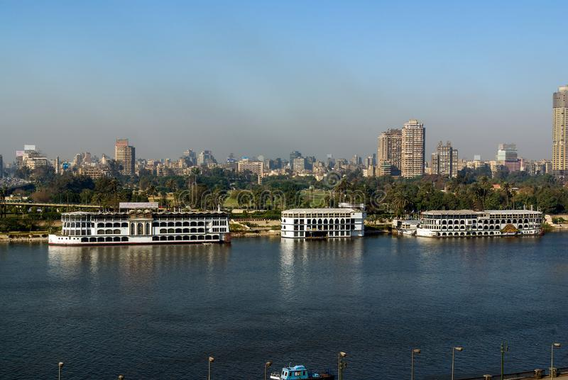 Nile River em sua maneira através da cidade do Cairo Egito com barcos amarrou na costa e na vista de construções modernas fotos de stock