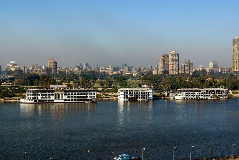 Nile River en su manera a través de la ciudad de El Cairo Egipto con los barcos amarró en la orilla y la vista de edificios moder fotos de archivo