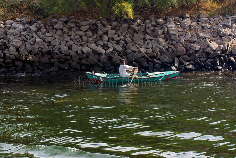 Nile river, near Aswan, February 16, 2017: fisherman paddling in a small boat in the dio, dressed in the typical Egyptian white an royalty free stock photo