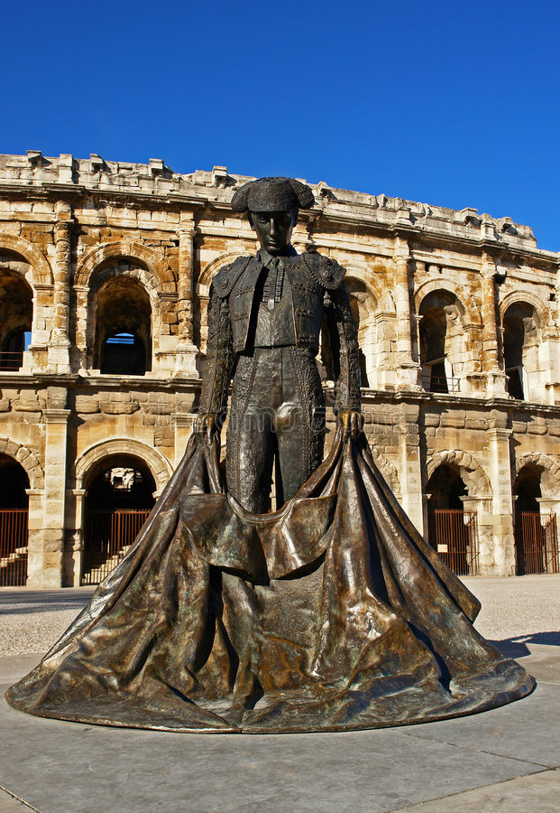 Nimes bullring and statue. Bullfighter statue with Arena of Nimes bullring in background, Nimes, France stock photo