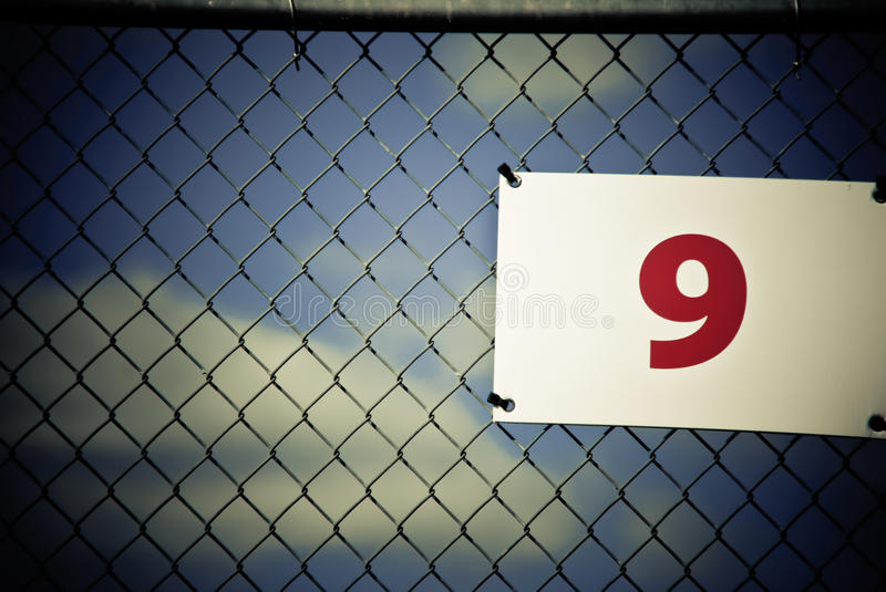 Nine. A sign with the number nine against a chain link fence with a blue sky and some clouds royalty free stock photography