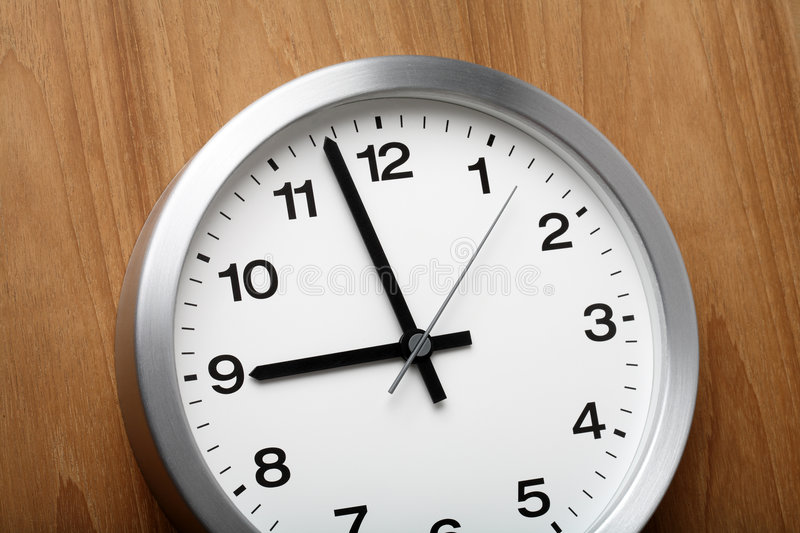 Almost nine. The aluminum wall clock is almost nine royalty free stock image