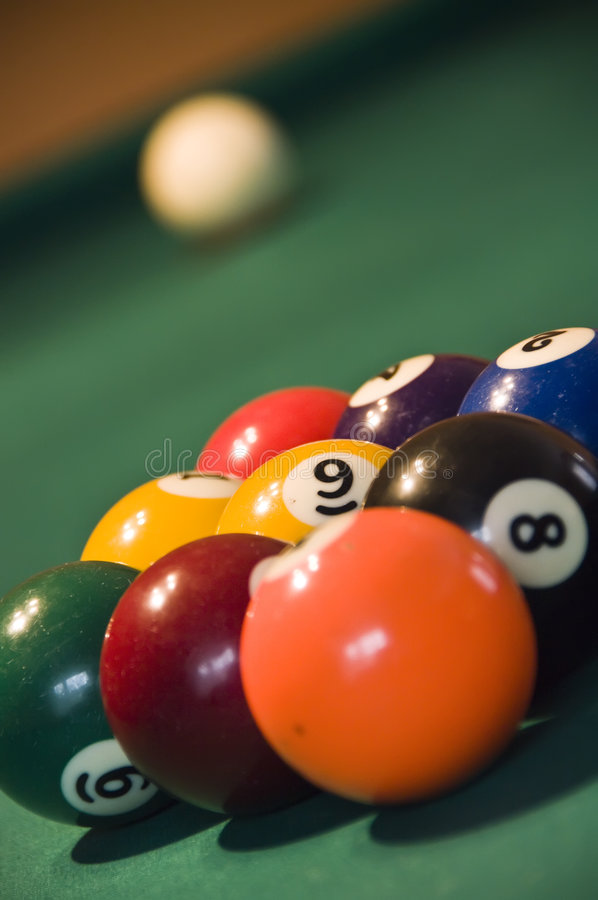 Nine balls pool. Closeup of nine balls of a pool game, white ball in the distance royalty free stock image