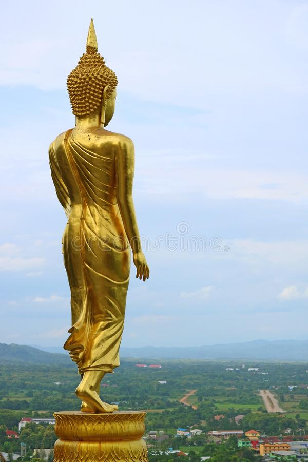 Nine metres high golden Buddha image in walking posture of Wat Phra That Khao Noi, a hilltop historic temple in Nan Province, Thai. Land, Thai culture royalty free stock photos