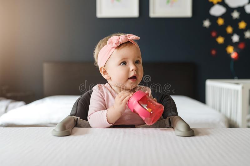 Nine-month-old smiling baby girl in pink bandage sits at white table in highchair and drinks water from baby`s cup. In background crib in soft focus royalty free stock photography