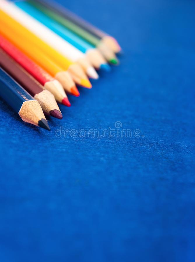 Nine multicolored pencils on a blue felt background. Different colored pencils with space for text. Back to school. Art lessons.  royalty free stock photos
