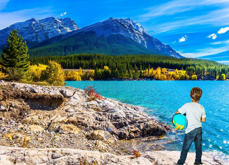 Nine-year-old boy with a globe in his hands. Exquisite Abraham Lake with turquoise water. Nine-year-old boy in jeans with a globe in his hands admires the lake royalty free stock photos