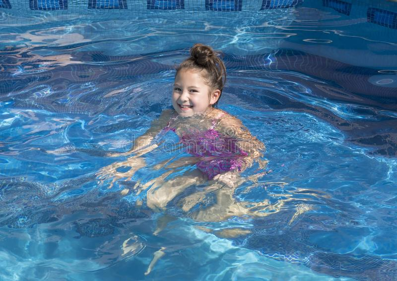Nine year-old girl treading water in a swimming pool. Pictured is a smiling nine year-old Amerasian girl treading water in a swimming pool at a vacation home in stock photography