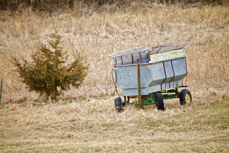 Nineteen Fifties Style Grain Wagon. A nineteen fifties style grain wagin sits in the dry grass beside the small pine tree royalty free stock photos