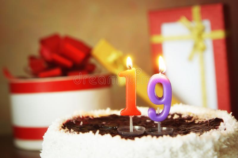 Nineteen years birthday. Cake with burning candle and gifts. Nineteen years birthday. Sweet cake with burning candle and gifts royalty free stock image