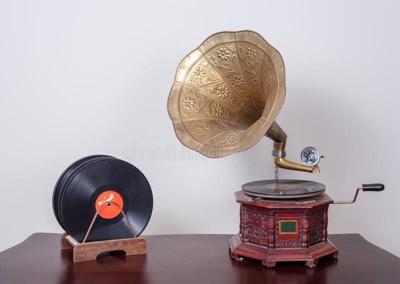 Nineteenth century phonograph gramophone and vinyl records on a wooden table and beige wall stock images