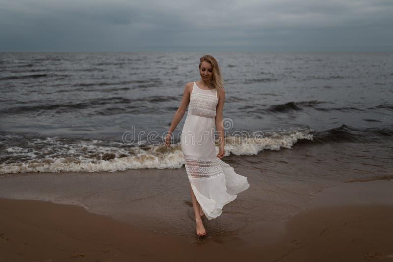 Ninfa loura nova bonita de passeio da praia da mulher no vestido branco perto do mar com ondas durante um tempo sombrio ma?ante c foto de stock
