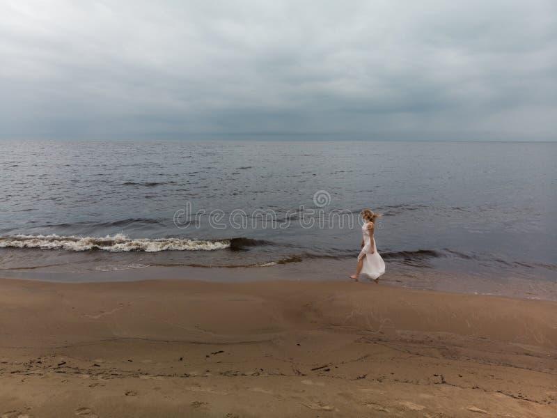 Ninfa loura nova bonita a?rea da praia da mulher no vestido branco perto do mar com ondas durante um tempo sombrio ma?ante com fotos de stock