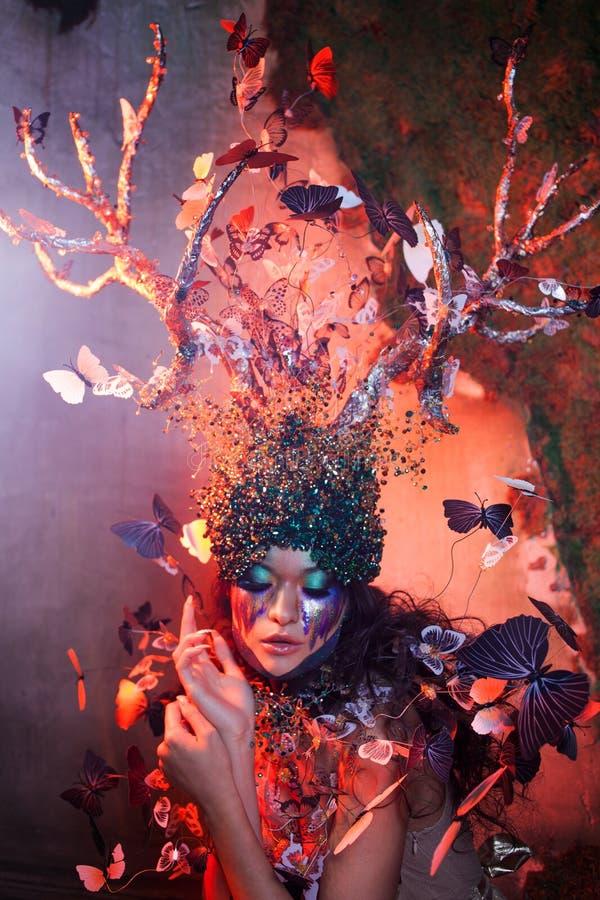 Ninfa natural con los cuernos como ramas de un árbol y de las mariposas que circundan alrededor Traje del estilo de la fantasía fotos de archivo