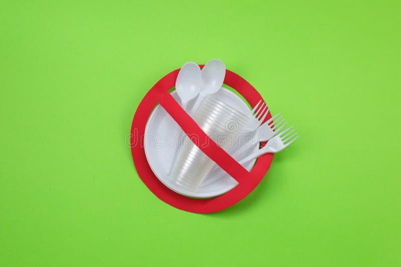 Ningún símbolo del uso en muestra prohibida roja con los platos plásticos en fondo verde Concepto ambiental imagen de archivo libre de regalías