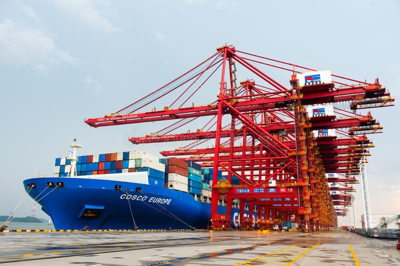 NINGBO ZHOUSHAN, CHINA - March 2018: Ningbo Zhoushan industrial shipping port on a busy day, cargo containers being. Loaded royalty free stock photo