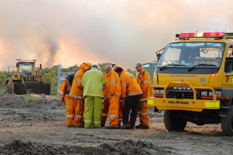 NINGI, AUSTRALIA - 9 DE NOVIEMBRE: Acercamientos dicussing del equipo del bombero para encender el frente arbusto fuego del 9 de n foto de archivo